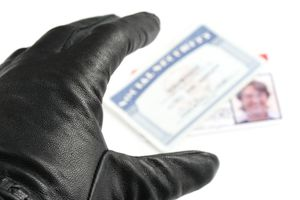 A gloved hand reaches for a Social Security card and ID card.