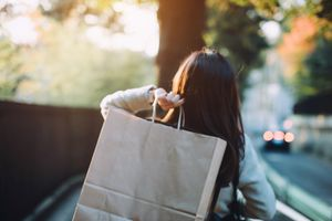 Rear view of woman carrying shopping bag over shoulder walking on city street