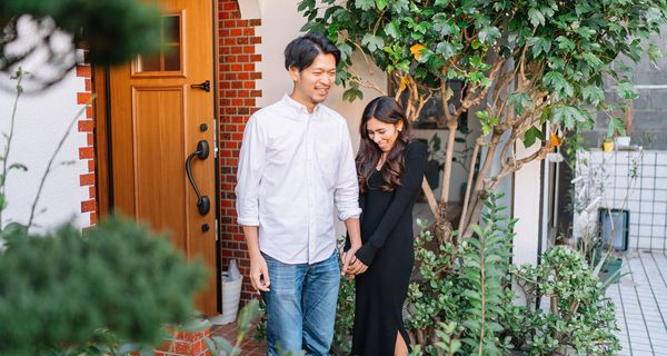 Young couple standing in front of their house happily
