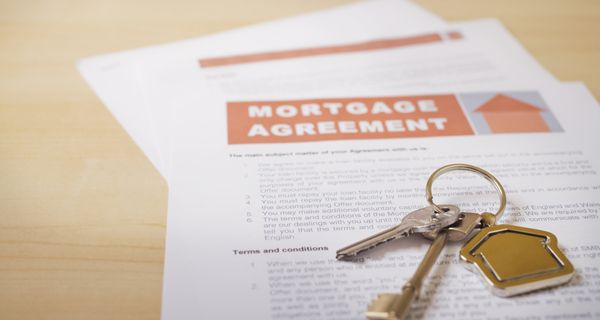House keys and mortgage loan agreement on desk, close-up.