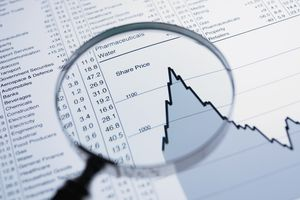A magnifying glass and descending line graph and list of share prices.