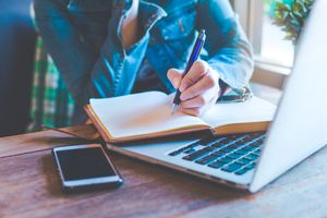 Student at desk, writing in journal on top of open laptop