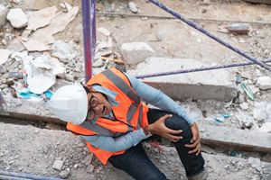 An injured construction worker clutching his knee
