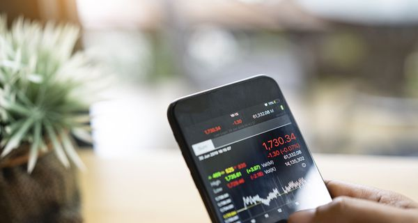 Disembodied Hands Holding a Smartphone with Stock Trading Information on the Screen