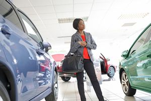 Young woman looking at cars in a showroom.