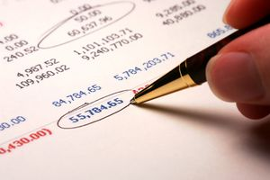 Cropped photo of a balance sheet containing numbers with some circled by a pen being held by someone
