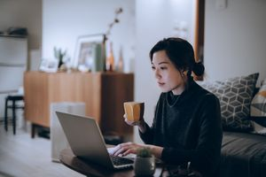 Young woman works on a laptop in her upscale home late into the evening.