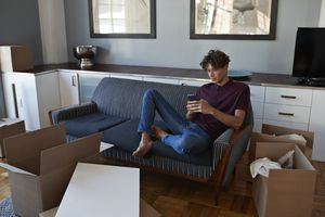 A renter sits on a couch texting, surrounded by open cardboard boxes in his new apartment