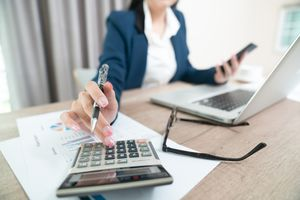 A female accountant sitting at the desk and using a calculator.