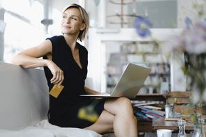 Woman sitting on a couch looking over her shoulder smiling with a laptop on her lap and a credit card in her hand