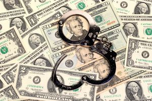 handcuffs sitting on top of US paper currency