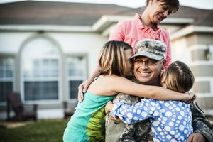 Mother watching over two daughters hugging their dad in military fatigues uniform in the front yard of their house.