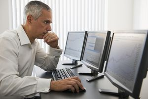 A broker working on three computers.