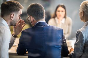 Businessperson whispering to a colleague during a meeting
