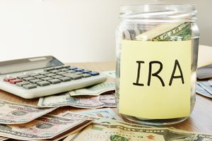 Table with cash, a calculator, and a jar labeled IRA on it