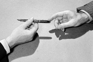 Businessmen pass a fountain pen, 1939