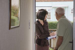 Researcher talking to elderly man on doorstep