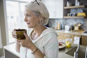 Older woman in hoody holding cup in both hands, standing in kitchen.