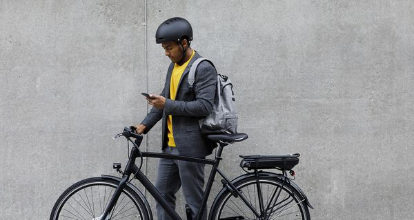 Young man standing by electric bicycle using smartphone