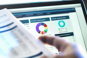 Investor checking performance of financial portfolio online while reviewing investment statement.
