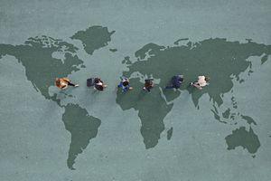 Businesspeople walking in line across world map, painted on asphalt