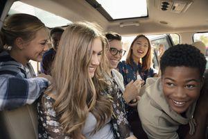 Playful teenagers pilling into car.