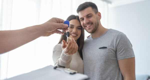 Hands of estate agent giving keys to renting couple