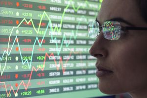 Analyst reviews stock market data on a monitor