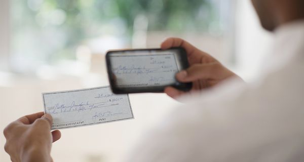 Man taking photo of a bank check with a mobile phone
