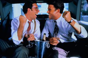 Stockbrokers drink champagne and celebrate success in a limousine