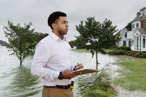 Insurance adjuster examining flooding damage to house