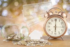 Digital Composite Image Of Currency By Alarm Clock And Hands At Table