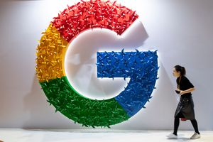 A woman passes a large sculpture of the Google logo at the first China International Import Expo (CIIE)