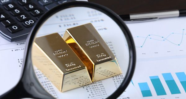 Image of gold bullion and magnifying glass