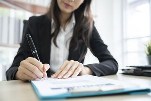 Woman signing papers on a desk in an office
