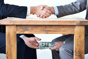 Corrupt businessmen exchange money under the table.