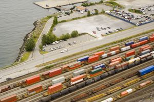 Overhead view of colorful freight train boxcars and flatbeds in a rail yard beside a parking lot.