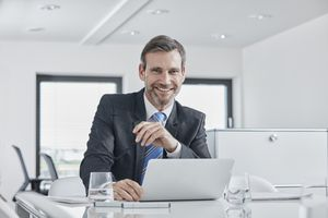A smiling businessman with laptop at desk in office.