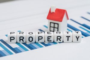 Cube block with alphabets building the word Property with small house on yearly chart and graph reports.