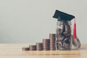 Coins in jar with money stack step growing.