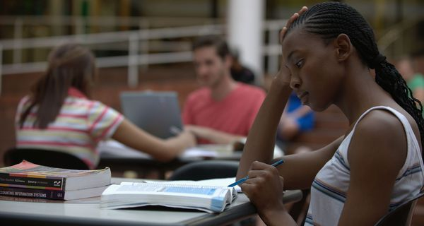 Female student studying with textbook with other students working at desks behind her.