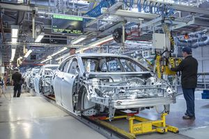 Workers on car production line in factory