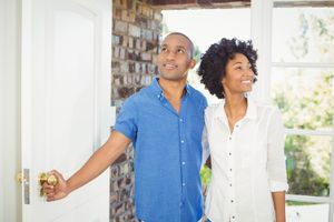 Smiling young couple entering a home