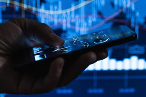 Cropped image of a hand holding a smartphone with financial data in front of a screen showing financial data charts