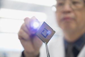 Focused Engineer Examining Microchip With Flashlight