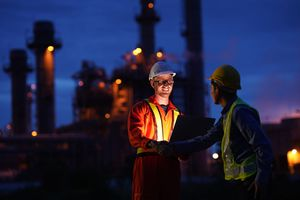 Handshake between an engineer and a foreman at night in front of a factory