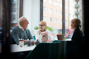 A smiling couple talking while sitting with a financial adviser in office.