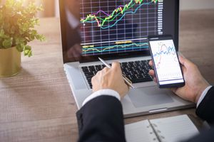 An investor analyzing stock market investments with financial dashboard.