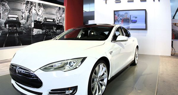 Tesla dealership with a white car and the Tesla logo in the background.