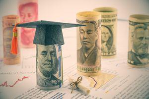 Graduation cap put on US 100 dollar bill.